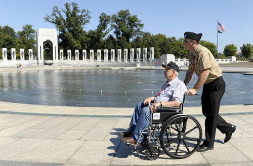 World War II veteran Gus Nicholas of Glendale Heights, Ill., is push by Navy Petty Officer First Class Lee Hoffman as they visit the World War II Memorial in Washington, Wednesday, Oct. 2, 2013. Nicholas came to Washington on an honor flight despite the shutdown of the federal government. It was an act of civil disobedience that marked the fact some barriers nor a government shutdown would keep a group of World War II veterans from visiting the monument erected in their honor. (AP Photo/Susan Walsh)