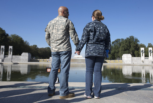 Chris and April Vannoy, of Woodbridge, Va., hold hands during a rally at the National World War II Memorial, Tuesday, Oct. 15, 2013, in Washington, held by the Military Coalition, a coalition of 33 of the leading veterans and uniformed services organizations, to demand an end to the partial government shutdown. April is currently serving the the Navy and Chris is going to school full and served in the Army. The federal government remains partially shut down and faces a first-ever default between Oct. 17 and the end of the month. (AP Photo/Carolyn Kaster)