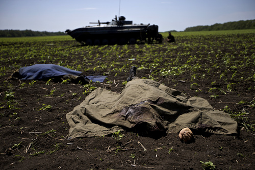 Bodies covered with blankets lie in a field near the village of Blahodatne, eastern Ukraine, on Thursday, May 22, 2014, as a Ukrainian soldier smokes next to his armored infantry vehicle. At least 11 Ukrainian troops were killed and about 30 others were wounded when Pro-Russians attacked a military checkpoint, the deadliest raid in the weeks of fighting in eastern Ukraine. Three charred Ukrainian armored infantry vehicles, their turrets blown away by powerful explosions, and several burned vehicles stood at the site of the combat. (AP Photo/Ivan Sekretarev)