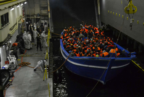 In this photo released by the Italian Navy on May 22, 2014, a fishing boat filled with migrants is towed into the Navy ship San Giorgio headed to Sicily. (AP Photo/Italian Navy, ho)