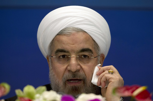 "Iranian President Hassan Rouhani wipes his cheek as he speaks during a press conference at a hotel in Shanghai, China, Thursday, May 22, 2014. Rouhani says an agreement on curbing its nuclear program is ""very likely"" by July despite a snag in talks last week, but said negotiations might also be extended. (AP Photo/Ng Han Guan)"