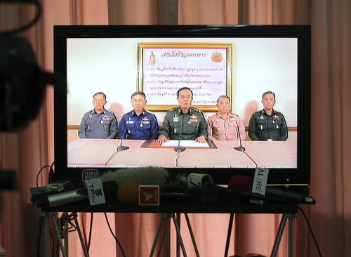 Thai Army Chief Gen. Prayuth Chan-Ocha, center, and other high ranking Thai officers are shown on television announcing the military takeover in Bangkok, Thailand Thursday, May 22, 2014. Thailand's army chief announced a military takeover of the government Thursday, saying the coup was necessary to restore stability and order after six months of political deadlock and turmoil. They are from left, National Police Chief Gen. Adul Saengsingkaew, Air Force Chief Air Chief Marshal Prachin Chanthong, Prayuth, Navy Chief Adm. Narong Pipatthanasant and an unidentified soldier from the Supreme Command Office. (AP Photo/Apichart Weerawong)
