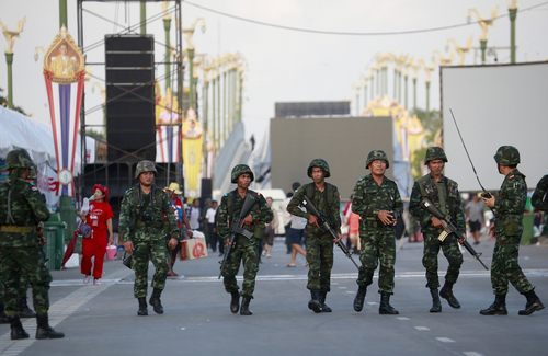 Thai soldiers move in to a demonstration site of the pro-government Red Shirt group and order the demonstrators to disperse on the outskirts of Bangkok, Thailand Thursday, May 22, 2014. Thailand's army chief Gen. Prayuth Chan-ocha announced a military takeover of the government Thursday, saying the coup was necessary to restore stability and order after six months of political deadlock and turmoil. (AP Photo/Wason Wanichakorn)