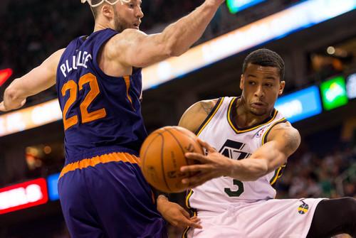 Trent Nelson  |  The Salt Lake Tribune Utah Jazz point guard Trey Burke (3) passes around Phoenix Suns center Miles Plumlee (22) as the Utah Jazz host the Phoenix Suns, NBA Basketball in Salt Lake City, Wednesday, February 26, 2014.