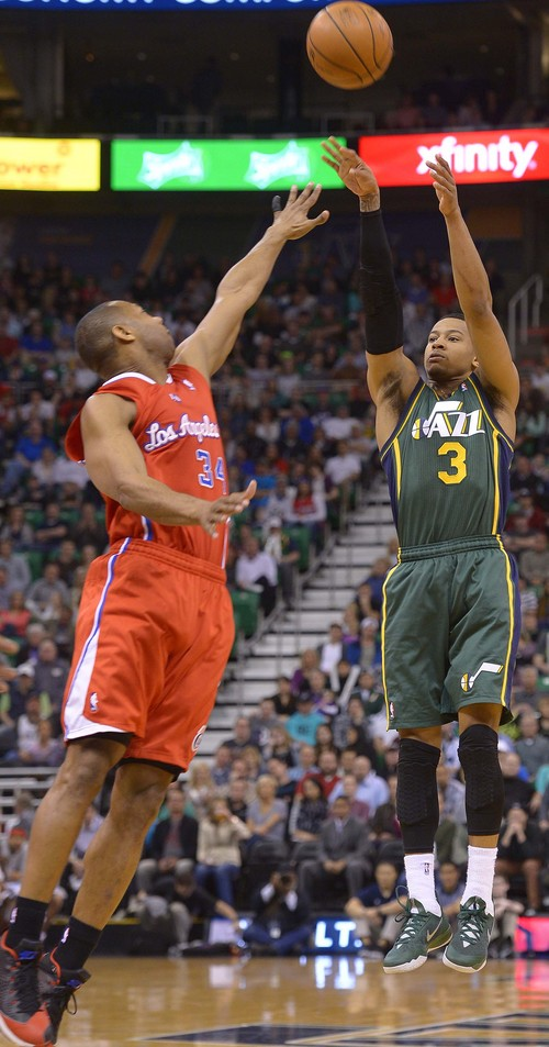 Leah Hogsten  |  The Salt Lake Tribune Utah Jazz guard Trey Burke (3) fires off a 3-point shot. Utah Jazz lead the Los Angeles Clippers 51-43 at the half during their game, Friday, March, 14, 2014 at Energy Solutions Arena.