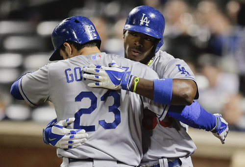 Los Angeles Dodgers' Yasiel Puig, right, is greeted by Adrian Gonzalez (23) after hitting a solo home run against the New York Mets during the sixth inning of a baseball game, Wednesday, May 21, 2014, in New York. (AP Photo/Julie Jacobson)