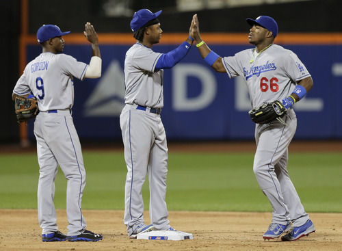 Los Angeles Dodgers right fielder Yasiel Puig (66) high fives shortstop Hanley Ramirez (13) and  second baseman Dee Gordon (9) after the Dodgers beat the New York Mets 9-5 in a baseball game, Tuesday, May 20, 2014, in New York. (AP Photo/Julie Jacobson)