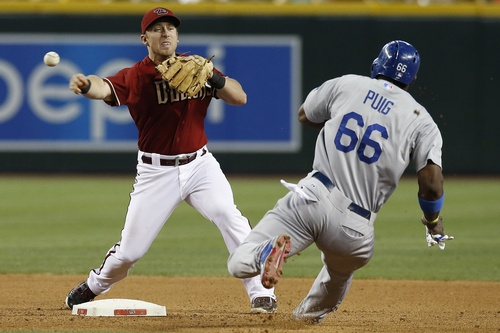 Arizona Diamondbacks' Cliff Pennington, left, forces Los Angeles Dodgers' Yasiel Puig (66) out at second base during the eighth inning of a baseball game on Sunday, May 18, 2014, in Phoenix.  The Diamondbacks defeated the Dodgers 5-3. (AP Photo/Ross D. Franklin)