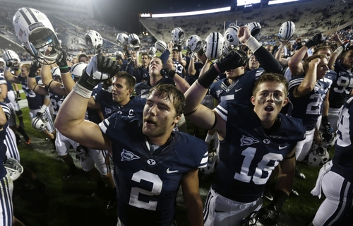 FILE - In this Sept. 7, 2013, file photo, Brigham Young's Spencer Hadley (2) and DJ Doman (18) celebrate with other players following their NCAA college football game against Texas, in Provo, Utah. Hadley, a suspended BYU football player, says he violated the school's honor code by drinking alcohol and partying in Las Vegas. Sports Illustrated reports Wednesday that the 23-year-old is ashamed of his actions. The senior linebacker from Connell, Wash., missed last weekend's game against rival Utah and can't rejoin the team until the Cougars play Boise State on Oct. 25 at the earliest. (AP Photo/Rick Bowmer, File)