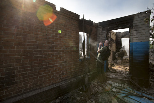 A journalist films a destroyed house following a mortar attack in Semyonovka village, outside Slovyansk, Ukraine, Friday, May 23, 2014. The village on the outskirts of Slovyansk, a city which has been the epicenter of clashes for weeks, has seen continuous shelling by the Ukrainian government forces, who have retaliated to the rebel fire. On Friday, the private house was destroyed by mortar fire that came from the Ukrainian side. There were no casualties, as the family living there had left the previous day, according to local residents. (AP Photo/Alexander Zemlianichenko)