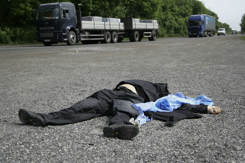 A body of a Ukrainian national guard member lies on a road in the village of Karlivka, some 40 kilometers (25 miles) west of the city of Donetsk, eastern Ukraine, on Friday May 23, 2014.  At least three people died when Ukrainian national guard unit and pro-Russian militiamen fought in the village of Karlivka early Friday. (AP Photo/Alexander Ermochenko)