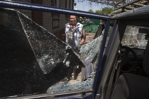 A local woman walks past a broken car inside her yard, after a shelling from Ukrainian government forces in Slovyansk, Ukraine, Friday, May 23, 2014. The village of Semenovka on the outskirts of Slovyansk, a city that has been the epicenter of clashes for weeks, has seen continuous shelling by the Ukrainian government forces retaliating to rebel fire. Shelling continued later in the day, targeting Slovyansk, where several other buildings were also damaged. There was no word of casualties. (AP Photo/Alexander Zemlianichenko)