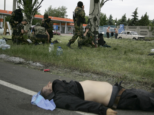A body of a Ukrainian national guard member, who was killed during a gunfight in the village of Karlivka earlier, lies on a road as armed Pro-Russian men rest, in Donetsk, eastern Ukraine, on Friday, May 23, 2014.  At least three people died when Ukrainian national guard unit and pro-Russian militiamen fought in the village of Karlivka early Friday. (AP Photo/Alexander Ermochenko)
