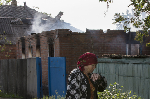 An elderly local woman passes a house destroyed by shellings in Semyonovka village, outside Slovyansk, Ukraine, Friday, May 23, 2014. The village on the outskirts of Slovyansk, a city which has been the epicenter of clashes for weeks, has seen continuous shelling by the Ukrainian government forces, who have retaliated to the rebel fire. On Friday, a private house was destroyed by mortar fire that came from the Ukrainian side. There were no casualties, as the family living there had left the previous day, according to local residents. (AP Photo/Alexander Zemlianichenko)