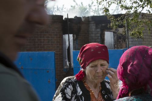 Local citizens talk to each other in front of a house destroyed by shellings in Semyonovka village, outside Slovyansk, Ukraine, Friday, May 23, 2014. The village on the outskirts of Slovyansk, a city which has been the epicenter of clashes for weeks, has seen continuous shelling by the Ukrainian government forces, who have retaliated to the rebel fire. On Friday, a private house was destroyed by mortar fire that came from the Ukrainian side. There were no casualties, as the family living there had left the previous day, according to local residents. (AP Photo/Alexander Zemlianichenko)