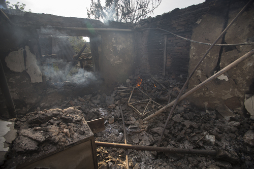 A destroyed house, following a motor attack, is seen in Semyonovka village, outside Slovyansk, Ukraine, Friday, May 23, 2014. The village on the outskirts of Slovyansk, a city which has been the epicenter of clashes for weeks, has seen continuous shelling by the Ukrainian government forces, who have retaliated to the rebel fire. On Friday, a private house was destroyed by mortar fire that came from the Ukrainian side. There were no casualties, as the family living there had left the previous day, according to local residents. (AP Photo/Alexander Zemlianichenko)