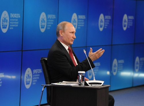 """Russian President Vladimir Putin speaks during a plenary session of the St. Petersburg International Investment Forum Friday, May 23, 2014. Speaking at the investment forum, Putin blamed the West for encouraging a """"coup"""" in Ukraine, when the nation's pro-Russian president was chased from power after months of protests. He said that Ukraine is now facing """"chaos and a full-scale civil war.""""  (AP Photo/RIA Novosti Kremlin, Mikhail Klimentyev, Presidential Press Service)"""