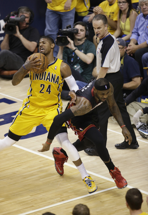 Indiana Pacers forward Paul George (24) goes after a loose ball with Miami Heat forward LeBron James during the first half of Game 2 of the NBA basketball Eastern Conference finals in Indianapolis, Tuesday, May 20, 2014. (AP Photo/AJ Mast)