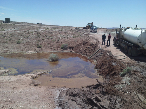 | Courtesy Bureau of Land Management  Crews on Thursday suck contaminated water from a containment pond after a 45-year-old oil well in Grand County spewed fluid for at least 30 hours. The well was capped and fluid contained before it could reach the nearby Green River.