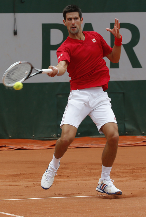 Novak Djokovic, of Serbia, returns the ball during a training session for the French Open tennis tournament, at the Roland Garros stadium in Paris, Friday, May 23, 2014. The French Open tennis tournament starts Sunday. (AP Photo/Michel Euler)