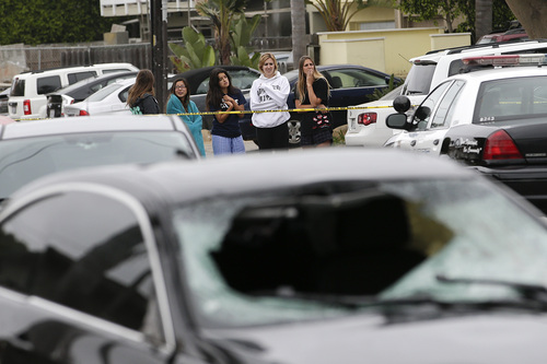 Onlookers gather near a black BMW sedan driven by a drive-by shooter on Saturday, May 24, 2014, in Isla Vista, Calif. The shooter went on a rampage near a Santa Barbara university campus that left seven people dead, including the attacker, and seven others wounded, authorities said Saturday. (AP Photo/Jae C. Hong)