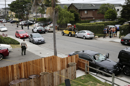 A deputy sheriff walks near a black BMW sedan driven by a drive-by shooter on Saturday, May 24, 2014, in Isla Vista, Calif. The shooter went on a rampage near a Santa Barbara university campus that left seven people dead, including the attacker, and seven others wounded, authorities said Saturday. (AP Photo/Jae C. Hong)
