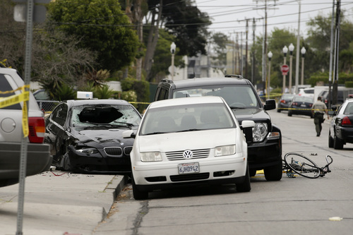 Police tap marks of the scene where a black BMW sedan, left, driven by a drive-by shooter, rests on Saturday, May 24, 2014, in Isla Vista, Calif. The shooter went on a rampage near a Santa Barbara university campus that left seven people dead, including the attacker, and others wounded, authorities said Saturday. (AP Photo/Jae C. Hong)