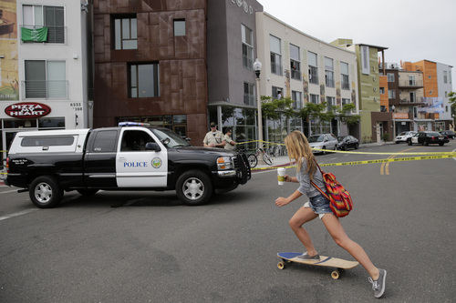 A woman rides her skateboard past the scene of a shooting on Saturday, May 24, 2014, in Isla Vista, Calif. A drive-by shooter went on a rampage near a Santa Barbara university campus that left seven people dead, including the attacker, and others wounded, authorities said Saturday. (AP Photo/Jae C. Hong)