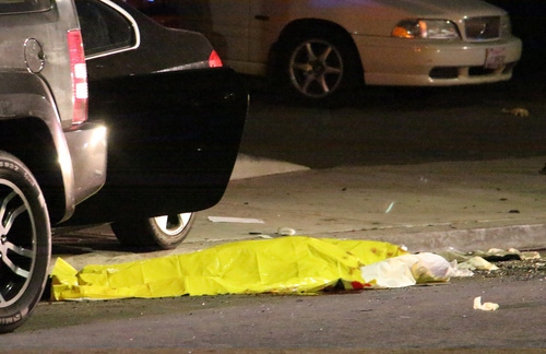 """In this image provided by KEYT-TV, a body is covered on the ground after a mass shooting near the campus of the University of Santa Barbara in Isla Vista, Calif., Friday, May 23, 2014.  A drive-by shooter went on a """"mass murder"""" rampage near the Santa Barbara university campus that left seven people dead, including the attacker, and seven others wounded, authorities said Saturday. (AP Photo/KEYT, John Palminteri)"""