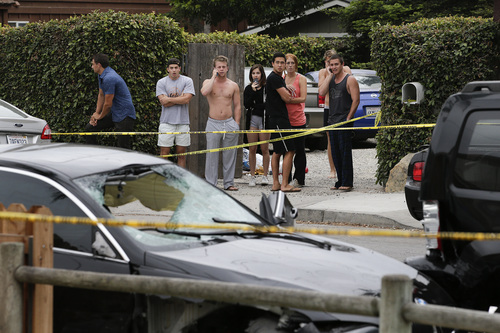 People look at a black BMW sedan driven by a drive-by shooter on Saturday, May 24, 2014, in Isla Vista, Calif. The shooter went on a rampage near a Santa Barbara university campus that left seven people dead, including the attacker, and seven others wounded, authorities said Saturday. (AP Photo/Jae C. Hong)