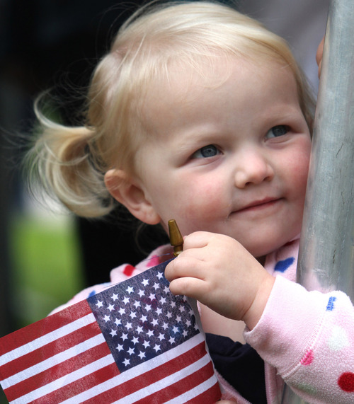 """Rick Egan      The Salt Lake Tribune  In this file photo from Memorial Day 2011, 3-year-old AidaMae Cowley holds an American Flag as she listens Angelle Brown sing """"God Bless America""""  during services at the Veterans Cemetery in Bluffdale."""