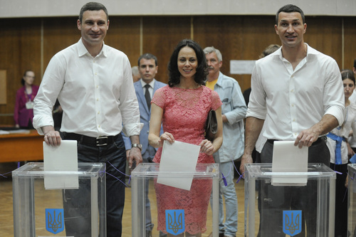 Vitali Klitschko, left, Kiev's mayoral candidate, his wife Natalia, center, and his brother boxer Wladimir Klitschko cast their ballots at a polling station during presidential and mayoral elections in Kiev, Ukraine, Sunday, May 25, 2014. Ukraine's critical presidential election got underway Sunday under the wary scrutiny of a world eager for stability in a country rocked by a deadly uprising in the east. (AP Photo/Evgeniy Maloletka)