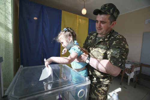 A Ukrainian soldier with his daughter, casts his ballot during voting in the presidential election at a polling station in the village of Kovyri in the Lviv region of western Ukraine, Sunday, May 25, 2014. Ukraine's critical presidential election got underway Sunday under the wary scrutiny of a world eager for stability in a country rocked by a deadly uprising in the east. (AP Photo/ Petro Zadorozhnyy)