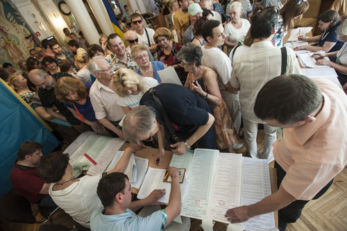 Ukrainians stand in line to receive their ballots at a polling station during presidential and mayoral elections in Kiev, Ukraine, Sunday, May 25, 2014. Ukraine's critical presidential election got underway Sunday under the wary scrutiny of a world eager for stability in a country rocked by a deadly uprising in the east. (AP Photo/Evgeniy Maloletka)