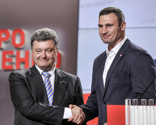 CORRECTS TO REFLECT THAT KIEV MAYOR RACE HAS NOT BEEN CALLED - Ukrainian presidential candidate Petro Poroshenko, left, shake hands with Vitali Klitschko during their press conference in Kiev, Ukraine, Sunday, May 25, 2014. Exit polls suggested that billionaire candy-maker Poroshenko won Ukraine's presidential election. Results for the Kiev mayoral race, in which former boxing champion Klitschko is a candidate, were not available Sunday. (AP Photo/Mykola Lazarenko, Pool)
