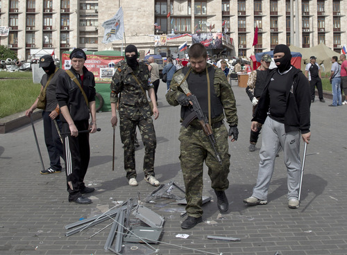 Pro-Russian militants stand by ballot boxes they smashed in front of the seized regional administration building in Donetsk, Ukraine, Sunday, May 25, 2014. Ukraine's critical presidential election got underway Sunday under the wary scrutiny of a world eager for stability in a country rocked by a deadly uprising in the east. While there were no immediate reports of violence, pro-Russia insurgents were trying to block voting by snatching ballot boxes and patrolling polling stations.(AP Photo/Vadim Ghirda)