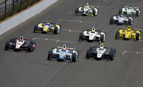 The field for the the 98th running of the Indianapolis 500 IndyCar auto race heads into the first turn, lead by James Hinchcliffe, of Canada, (27), Ed Carpenter (20) and Will Power, of Australia, (12) on the start at the Indianapolis Motor Speedway in Indianapolis, Sunday, May 25, 2014. (AP Photo/Darron Cummings)