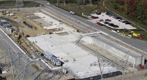 This Oct. 21, 2013 aerial photo released by Dominion Resources, shows an area where spent radioactive waste is stored at the Millstone Power Station in Waterford, Conn. Nineteen existing horizontal storage modules are on the right, and a new concrete pad to house more units is under construction, center. That construction was subsequently completed. With the collapse of a proposal for nuclear waste storage at Nevada's Yucca Mountain, Millstone and other plants across the country are building or expanding on-site storage for waste. (AP Photo/Dominion Resources)