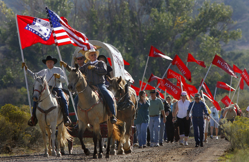 Steve Griffin  |  Tribune file photo Descendants of the victims of the Mountain Meadow Massacre (right) carry flags with their family names on them as they are led down the road by the Fancher Wagon Train, to the Mountain Meadow Massacre Memorial Grave Site, during the Mountain Meadows Massacre Memorial near Enterprise, Utah, Sept. 11, 2007.  The wagon train is sponsored by The Mountain Meadows Monument Foundation. The massacre happened on Sept. 11, 1857.