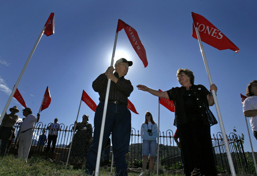 Steve Griffin  |  Tribune file photo  With tears in her eyes Jerilyn Jones Clayton (right) reaches out to comfort an emotional Bill Basham as they hold flags with their family names on them during the Mountain Meadows Massacre Memorial near Enterprise, Utah, Sept. 11, 2007.  Both Jerilyn Jones Clayton and Bill Basham are descendants of people who were killed in the massacre which happened on Sept. 11, 1857. The flag carrying descendants were led down a dirt road to the Mountain Meadows Massacre Grave Site by the Fancher Wagon Train as part of the memorial.