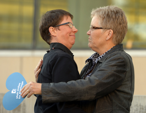 "Rick Egan  |  The Salt Lake Tribune  Plantiffs, Kody Partridge and Laurie Wood hug at the Utah Unites for Marriage ""send-off"" event Monday night at Library Square, Monday, April 7, 2014"
