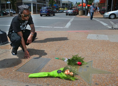 Quinntin Brown, 24, of St. Louis, pauses after laying a rose at Maya Angelou's star on the St. Louis Walk of Fame in The Loop in University City, Mo., Wednesday, May 28, 2014. Angelou, a Renaissance woman and cultural pioneer, has died Wednesday, her son said. She was 86. (AP Photo/St. Louis Post-Dispatch, David Carson)  EDWARDSVILLE INTELLIGENCER OUT; THE ALTON TELEGRAPH OUT