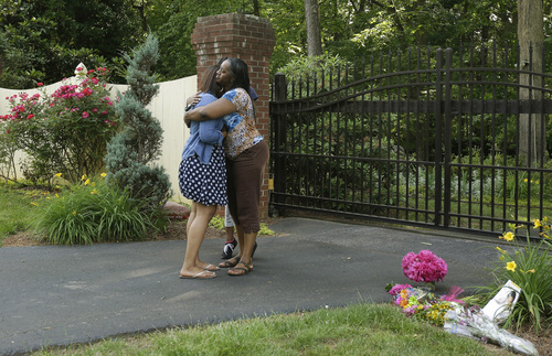 Dezmonee Selbey, left, is comforted by her mother Darretta Rhone as they stand outside the home of Maya Angelou in Winston-Salem, N.C., Wednesday, May 28, 2014. Angelou has died at the age of 86. (AP Photo/Gerry Broome)