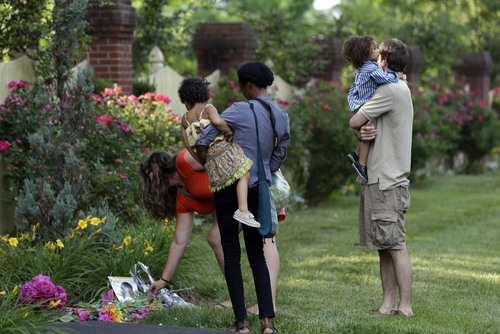 People visit a memorial outside the home of Maya Angelou in Winston-Salem, N.C., Wednesday, May 28, 2014.  Angelou has died at the age of 86. (AP Photo/Gerry Broome)
