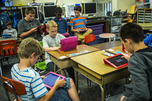Chris Detrick  |  The Salt Lake Tribune (Clockwise from front left) Sam Ford, Kobe Slack, Derek Jackson, Kadin Flinn, Salman Ali, Jered Harris, and Alizon Ramos use iPads to help learn about American history during Amber Palmer's class at Bennion Elementary School Tuesday May 6, 2014.