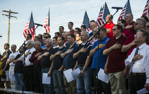 Chris Detrick  |  The Salt Lake Tribune Members of a men's choir watch as the flag is raised during a Memorial Day celebration at Hogan Park in Woods Cross on Monday, May 26, 2014.
