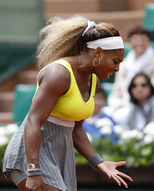 Serena Williams of the U.S. gestures after missing a return during the second round match of the French Open tennis tournament against Spain's Garbine Muguruza at the Roland Garros stadium, in Paris, France, Wednesday, May 28, 2014. (AP Photo/Darko Vojinovic)
