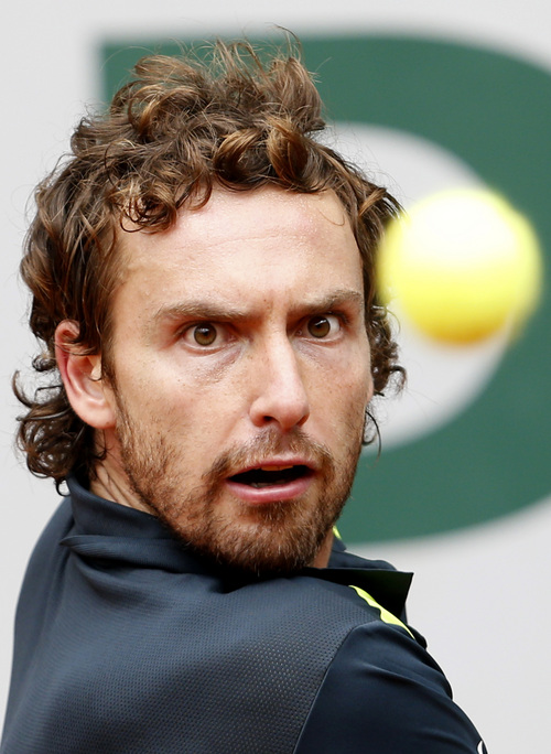 Latvia's Ernests Gulbis eyes the ball as he plays Argentina's Facundo Bagnis during their second round match of  the French Open tennis tournament at the Roland Garros stadium, in Paris, France, Wednesday, May 28, 2014. (AP Photo/Darko Vojinovic)