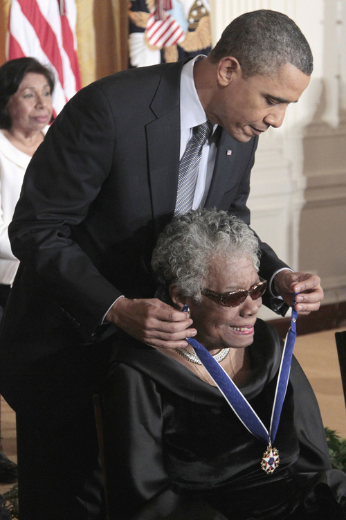 """FILE - This Feb. 15, 2011 file photo shows President Barack Obama kissing author and poet Maya Angelou after awarding her the 2010 Medal of Freedom during a ceremony in the East Room of the White House in Washington. President Barack Obama said Wednesday's passing of poet and author Maya Angelou has dimmed """"one of the brightest lights of our time."""" Obama said in a statement that he and first lady Michelle Obama will always cherish the time they were privileged to spend with Angelou. He says Angelou had the ability to remind us that we are all God's children and that we all have something to offer. (AP Photo/Pablo Martinez Monsivais, File)"""