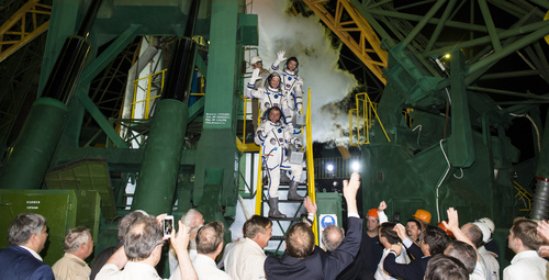 In this image released by NASA, European Space Agency's astronaut from Germany Alexander Gerst, top, Russian cosmonaut Maxim Suraev, bottom, and NASA astronaut Reid Wiseman, center, crew members of the latest mission to the International Space Station, ISS, wave farewell prior to boarding the Soyuz-FG  rocket at the Russian leased Baikonur cosmodrome, Kazakhstan, Wednesday, May 28, 2014. (AP Photo/NASA, Joel Kowsky) MANDATORY CREDIT